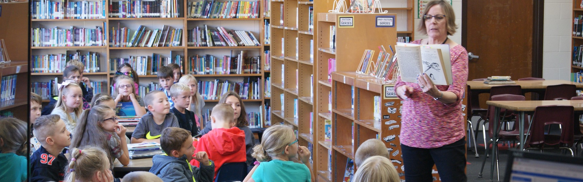 Librarian reads book to 2nd grade classroom in the library
