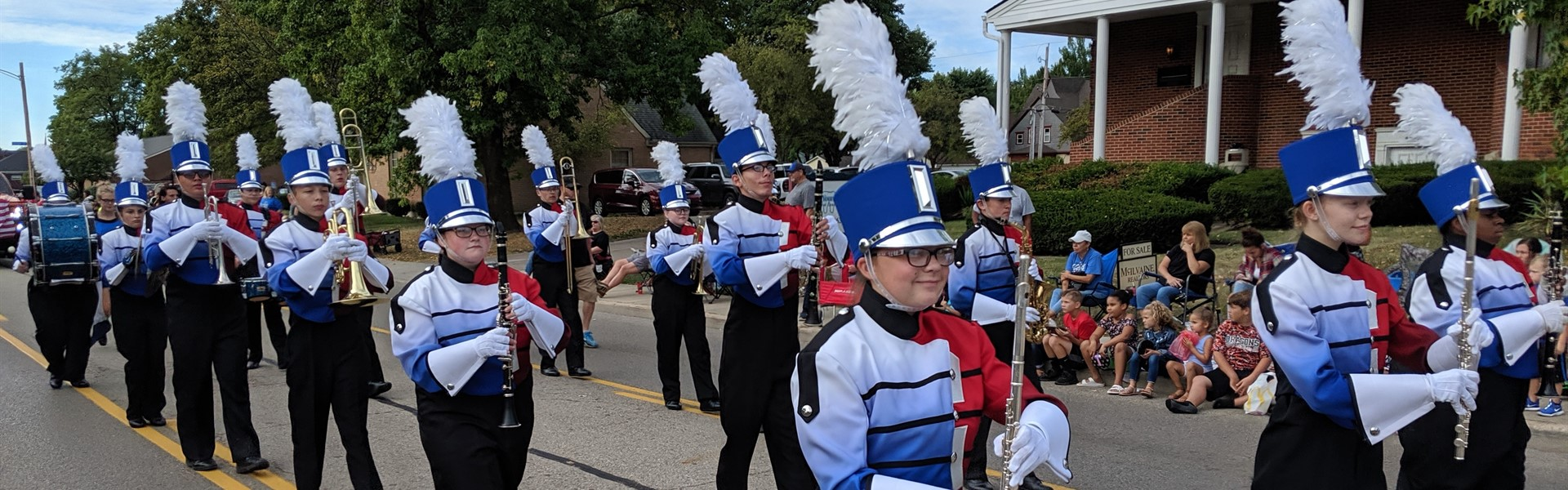 Marching Band in parade through Xenia in red, white, and blue uniforms